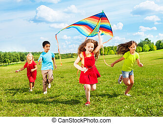 Kids run with kite - Group of four kids running in the park...