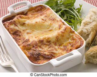 Dish of Lasgane with Salad Leaves and Italian Bread