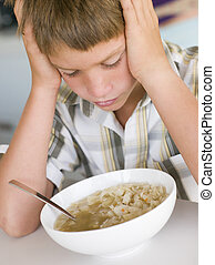 Young boy in kitchen eating soup