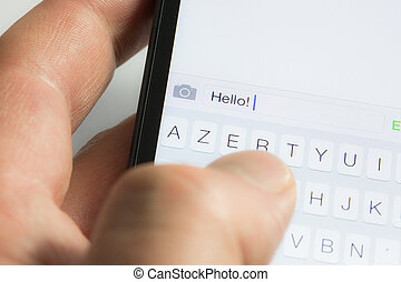Texting - closeup on sending a text message with a mobile...