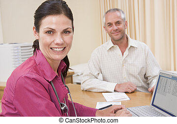 Doctor with laptop and man in doctor\'s office smiling