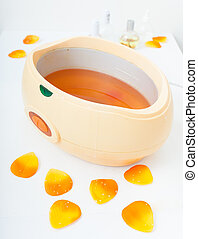 Orange paraffin wax in bowl spa - Orange paraffin wax in...