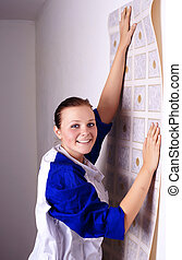 young woman tries on wall-papers to wall