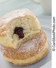 Two Raspberry Jam Doughnuts with a bite