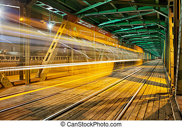Steel Truss Bridge with Tram Light Trail - Abstract tram...