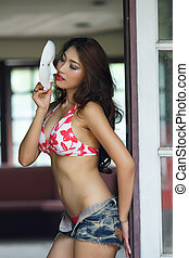 Young beautiful Asian woman in red bikini with short pants...