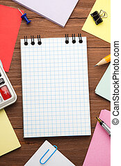 checked notepad and office accessories on wood background