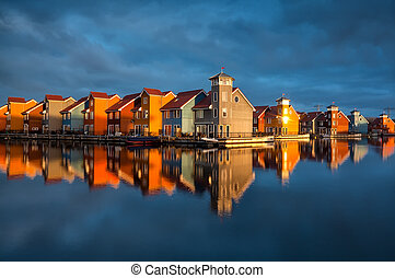 beautiful colorful buildings on water in gold sunshine,...