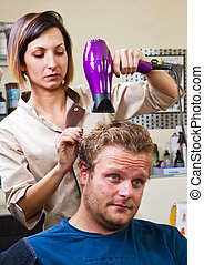 Beautiful man at the hairdresser blow drying his hair