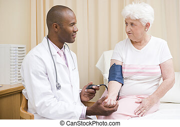 Doctor checking woman\'s blood pressure in exam room