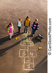Friends play outside on hopscotch - Group of kids jumping on...