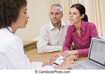 Doctor with laptop and couple in doctors office frowning