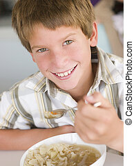 Young boy in kitchen eating soup and smiling