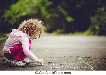 Child draws on asphalt
