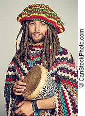 playing the drum - Portrait of a rastafarian guy playing his...
