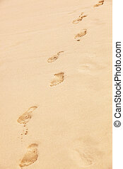 traces of bare feet on the sand beach