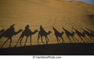 Erg Chebbi caravan shadows - Tourists are led through the...