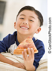 Young boy eating pizza slice in living room smiling