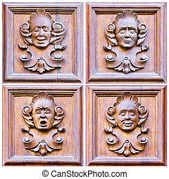 A set of four faces expressing different emotions over wood
