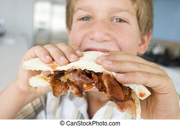 Young boy in kitchen eating bacon sandwich