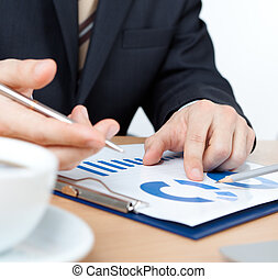 Businessman sitting at the table with documents, cup of...