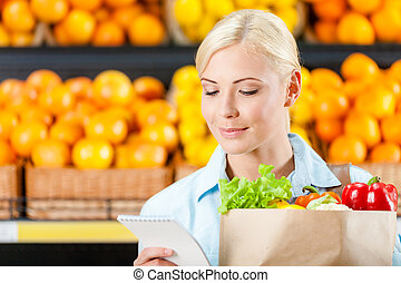 Girl hands bag with fresh vegetables reading list of products