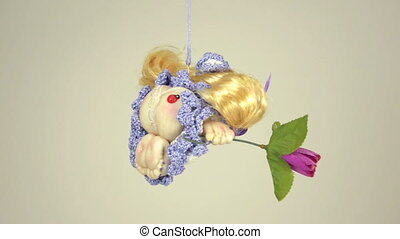 Little witch doll with a rose is turning on the rope