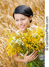 Close up of girl with flowers in the field - Close up of...