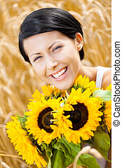 Close up of young girl with sunflowers in the field - Close...