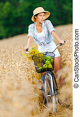 Girl rides cycle with apples and flowers in rye field - Girl...