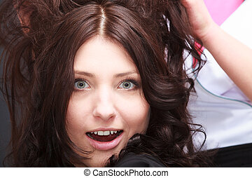 Surprised brunette woman open mouth wide eyed in hair salon...