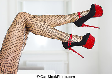 Legs of a woman wearing fishnet stockings and extreme red...