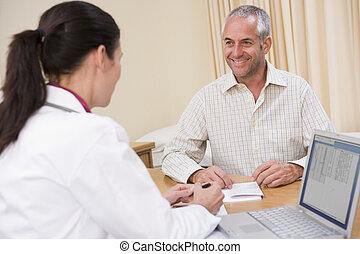 Doctor with laptop and man in doctors office smiling