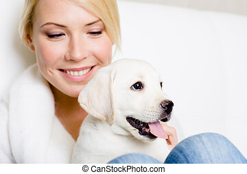 Close up of woman with puppy of labrador on her knees -...