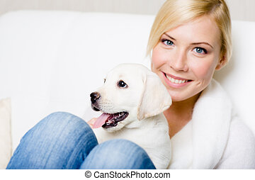 Close up of woman with white labrador puppy on her knees -...