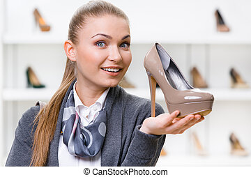Woman keeping coffee-colored stylish pump - Portrait of...