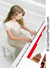 Top view of woman playing piano - Top view of woman wearing...