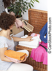 Woman arranging things in chest - Woman arranging different...