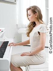 Profile of woman playing piano - Profile of woman wearing...