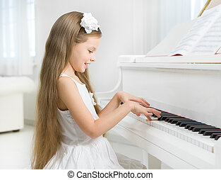 Profile of little girl in white dress playing piano. Concept...