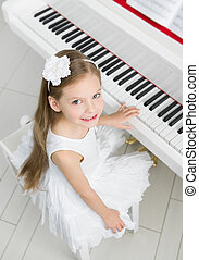 Top view of little musician in white dress playing piano -...