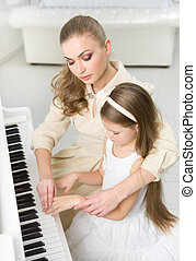 Music teacher teaches little girl to play piano - Tutor...