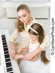 Music teacher teaches little girl to play piano - Tutor...