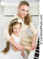 Musician teaches little girl to play piano - Tutor teaches...