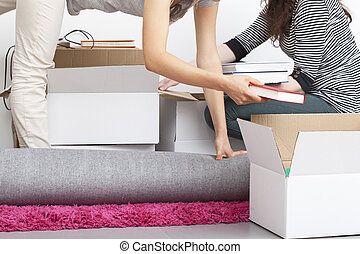 Tricky packing exercise - A woman packing things into a box...