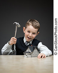 Little boy with house model and hammer - Portrait of little...