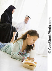 Young girl with fast food in living room with parents in...