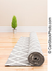 Unrolling carpet in a new home. Green plant in the...