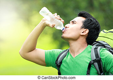 thirsty man drinking a bottle of water - hiking concept...