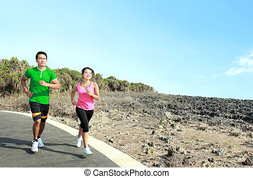 young couple running together on jogging track - Sporty...